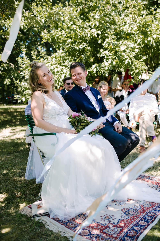 Brautpaar sitzt bei der freien Trauung auf einem Teppich unter Orangenbaeumen Freie Trauung im Essgarten Harpstedt.