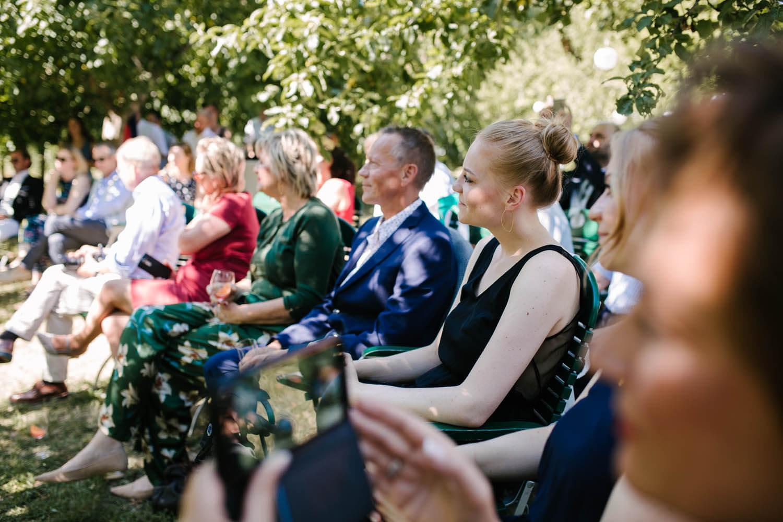 Gaeste schauen waehrend der freien Trauung das Brautpaar an. Freie Trauung im Essgarten Harpstedt.