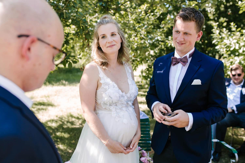 Brautpaar schaut den freien Trauredner an und hat die Hochzeitsringe in der Hand. Freie Trauung im Essgarten Harpstedt.