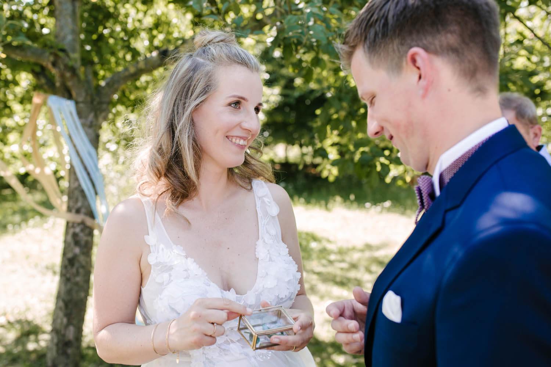 Braut schaut beim Tausch der Ringe verliebt den Braeutigam an.