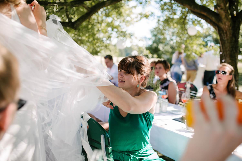Freundin der Braut holt Fliegen aus dem Hochzeitskleid. Freie Trauung im Essgarten Harpstedt.