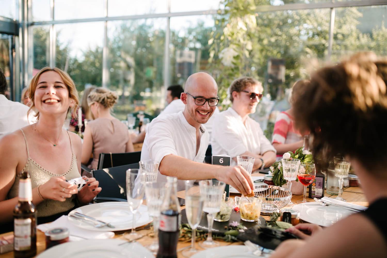 Lachende Gaeste im Essgarten von Harpstedt essen die Vorspeise. Freie Trauung im Essgarten Harpstedt.