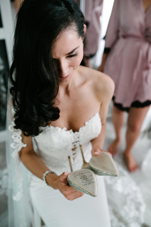 Braut ließt die Nachricht ihres Mannes auf der Unterseite der Jimmy Shoes. Hochzeit im Dom Osnabrück.