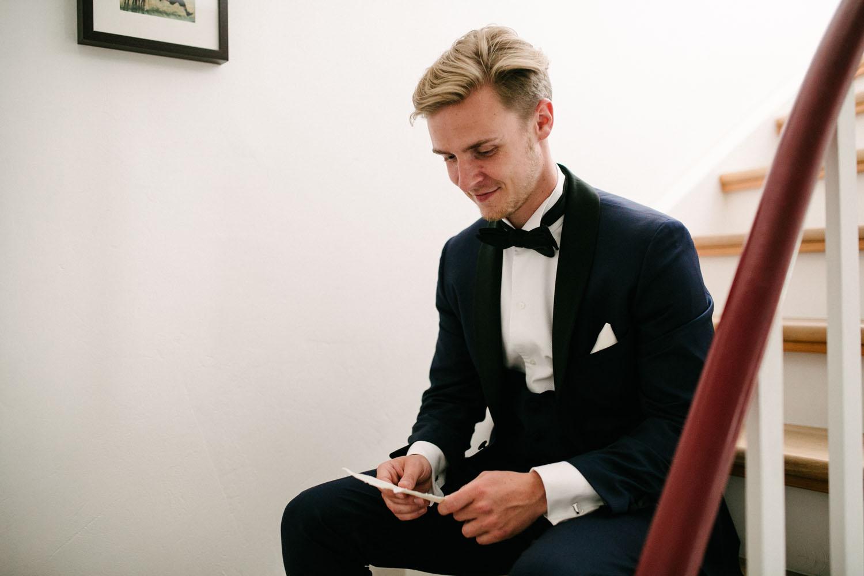 Braeutigam ließt einen Brief seiner zukuenftigen Frau auf der Treppe. Hochzeit im Dom Osnabrück.