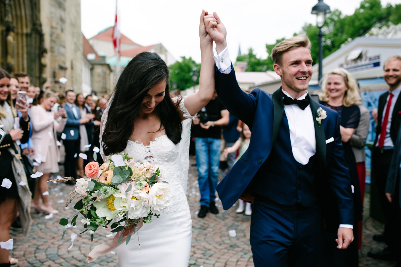 Brautpaar haelt die Haende bei dem Auszug aus der Kirche in die Höhe. Hochzeit im Dom Osnabrück.