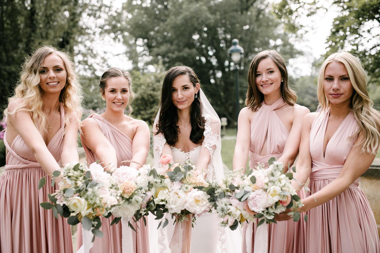 Braut haelt mit ihren Brautjungfern die Blumenstraeuße in die Kamera.