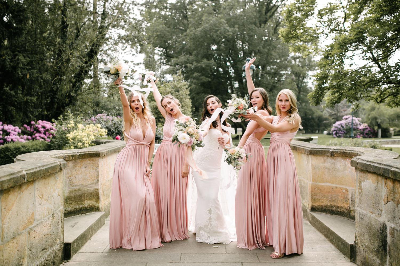 Braut jubelt mit ihren Brautjungfern bei dem Fotoshooting.
