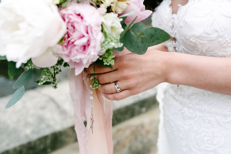 Nahaufnahme des Eheringes der Braut und des Brautstraußes.