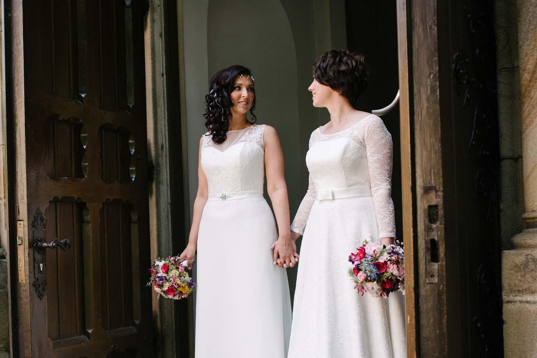 Zwei Braeute im Brautkleid Hand in Hand an der Tuer der Kirche. Hochzeit Stadtwaage