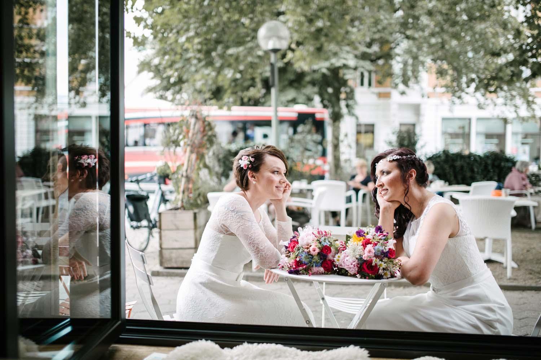 Blick durch ein geoeffnetes Fenster. Braeute am Tisch schauen sich verliebt an. Hochzeit Stadtwaage