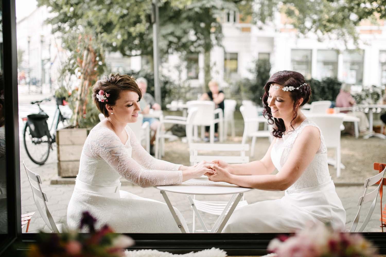 Braeute am Tisch halten Haendchen. Hochzeit Stadtwaage