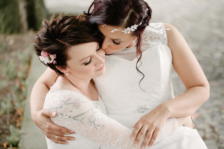 Braut sitzt auf dem Schoss der anderen und gibt ihr einen Kuss.Hochzeit Stadtwaage