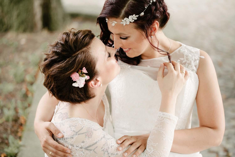 Braut sitzt auf dem Schoss der anderen und streicht ihr die Haare aus dem Gesicht. Hochzeit Stadtwaage
