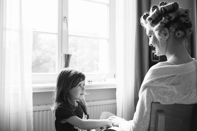 Braut haelt beim Getting Ready die Hand ihrer Nichte.