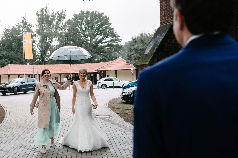 Braeutigam empfaengt Braut vor der Kirche. Hochzeit im Schloss Herten.
