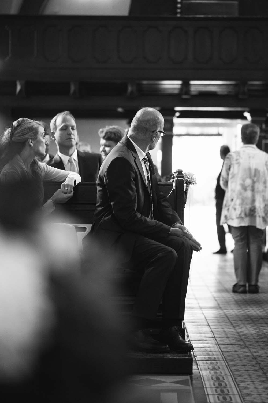 Brautvater dreht sich in der Kirche in der ersten Reihe nach der Braut um, bevor sie den Mittelgang entlanglaeuft.