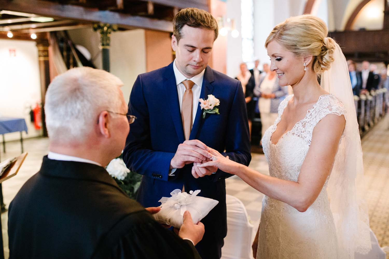 Braeutigam steckt seiner Braut den Ring an. der Pastor haelt im Vordergrund das Ringkissen.