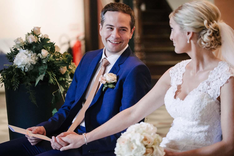 Braut und Braeutigam halten die Haende und laecheln sich gegenseitig an.