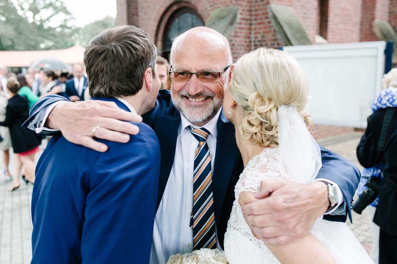 Umarmung des Brautpaars durch den Brautvater.