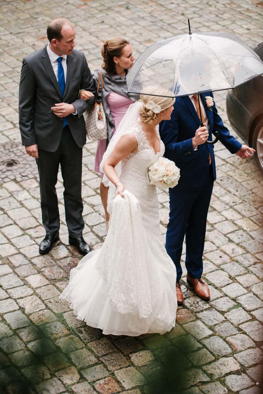 Brautpaar mit durchsichtigem Regenschirm an der Ankunft an der Location. Hochzeit im Schloss Herten.