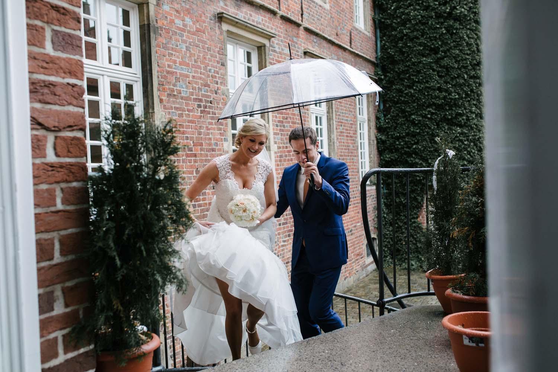 Brautpaar steigt die Treppe zur Location empor. Braeutigam haelt der Braut den Regenschirm. Hochzeit im Schloss Herten.