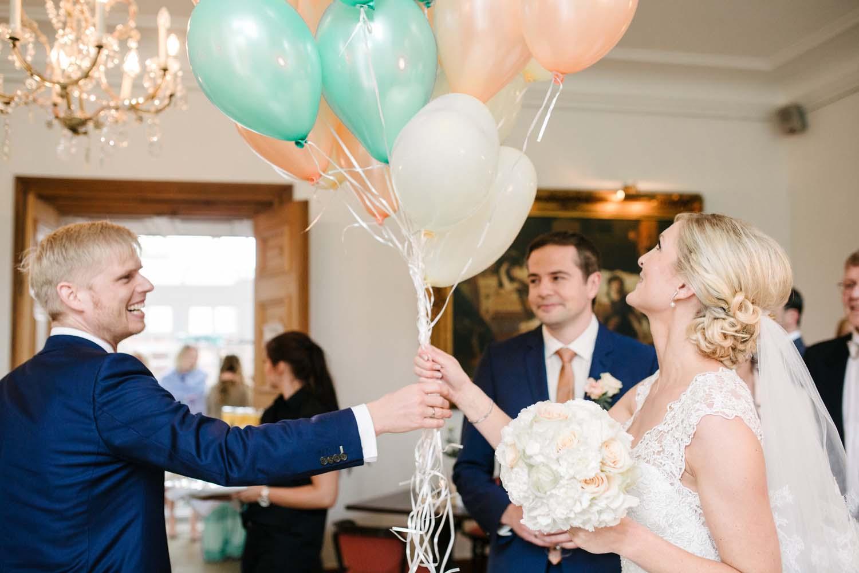 Trauzeuge uebergibt der Braut einen Strauss von Luftballons. Hochzeit im Schloss Herten.