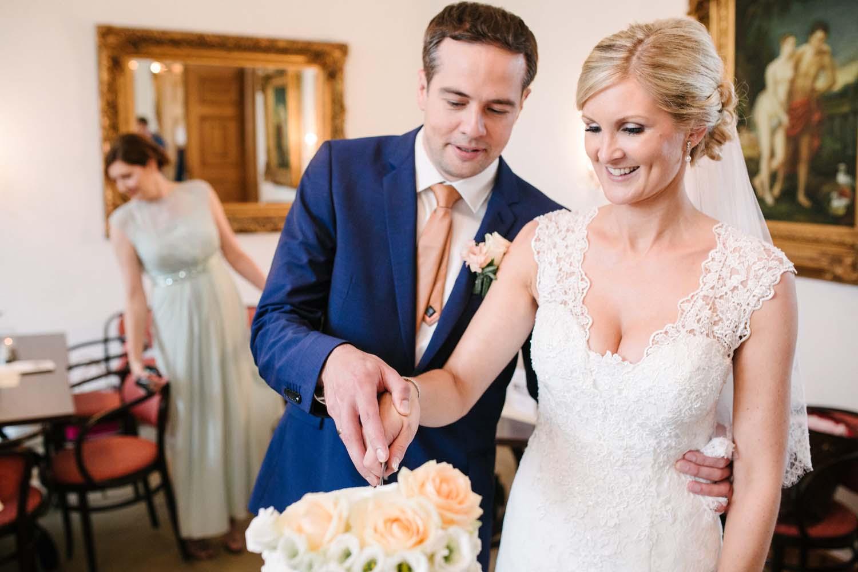Braut und Braeutigam schneiden die Hochzeitstorte an. Hochzeit im Schloss Herten.