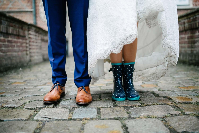 Nahaufnahme von Brautpaar in Gummistiefeln. Hochzeit im Schloss Herten.