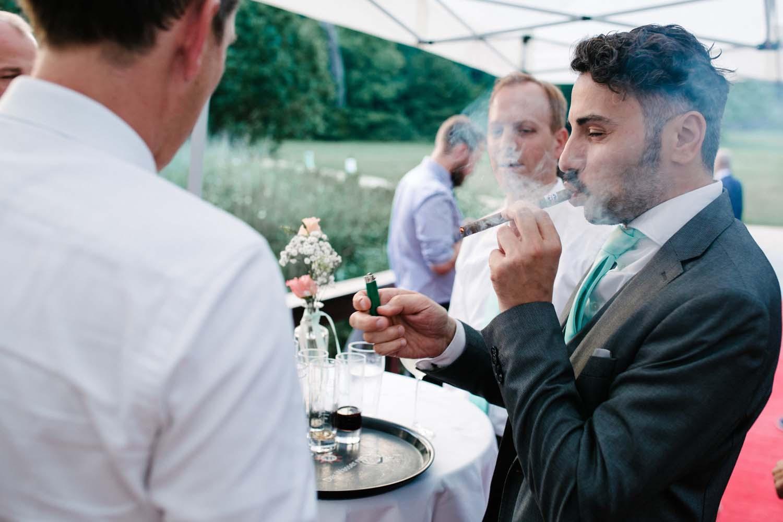 Gast zuendet sich eine Zigarre an. Hochzeit im Schloss Herten.