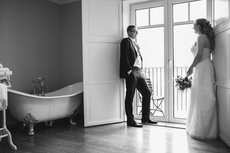 Brautpaar beim Hochzeitsshooting. Sie stehen sich im Hotelzimmer am Fenster gegenüber