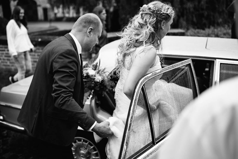 Braut steigt in den Brautwagen ein auf dem weg zur Hochzeitslocation.