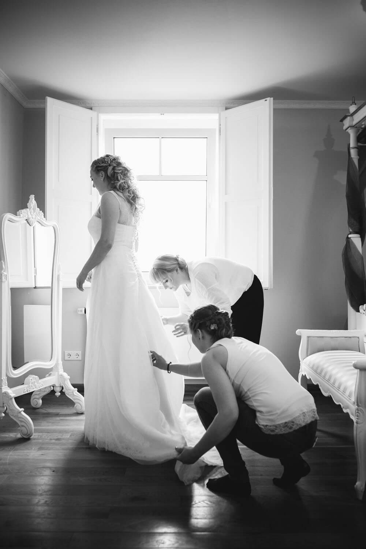 Brautjungfern helfen beim anziehen des Brautkleides.