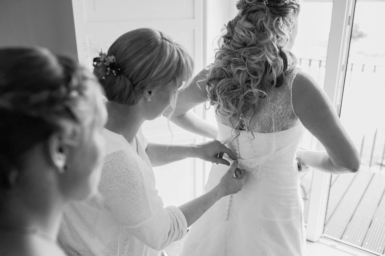 Braut vor dem Fenster. Brautjunger knöpft das Kleid.