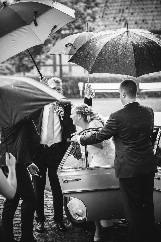 Braut steigt bei Regen aus dem Auto. Der Bräutigam hält den Schirm.
