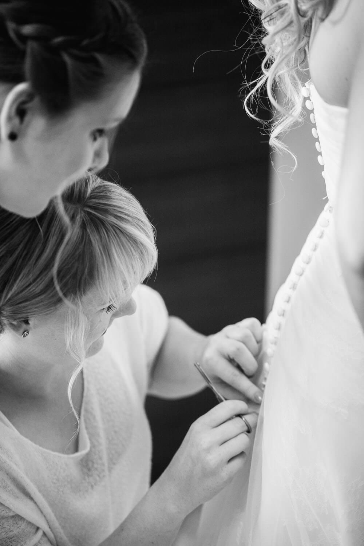 Brautjungfern knüpfen der Braut das Brautkleid. Hochzeitsfotograf Osnabrück Hochzeit im Beverland Resort.