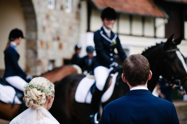 Pferdespalier im Hintergrund. Hochzeitspaar im Vordergrund von hinten gesehen.