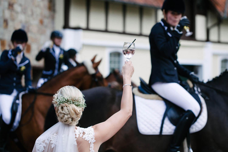 Braut prostet ihren Freundinnen auf Pferden im Hintergrund zu.