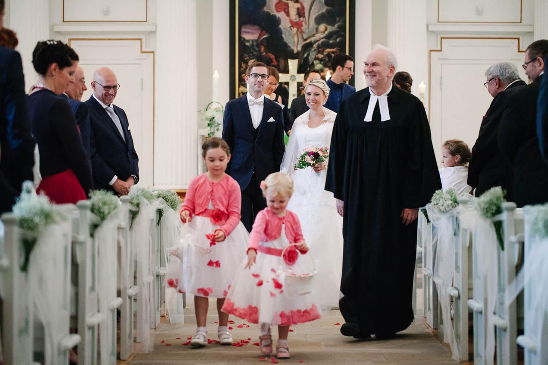 Brautpaar zieht aus der Kirche aus. Vor ihnen laufen zwei Blumenmädchen. Hochzeitsfotograf Osnabrück - Hochzeit von Maren und Kort