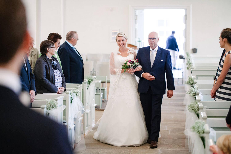 Braut und Vater ziehen gemeinsam in die Kirche. Bräutigam wartet im Vordergrund.