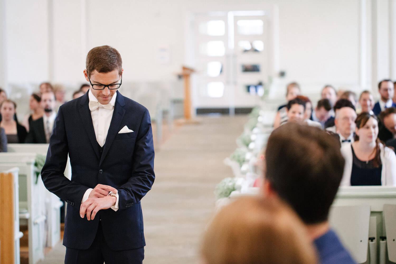 Bräutigam schaut in der Kirche auf seine Uhr, während er auf die Braut wartet.