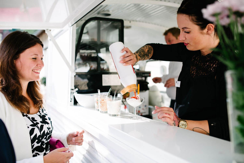Gäste am Frozen Yoghurt Wagen an der Hochzeitslocation.