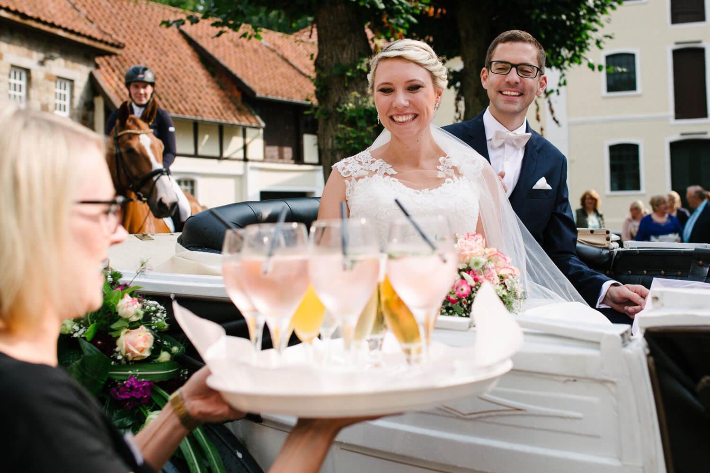 Brautpaar wird in der Kutsche mit Getränken empfangen.