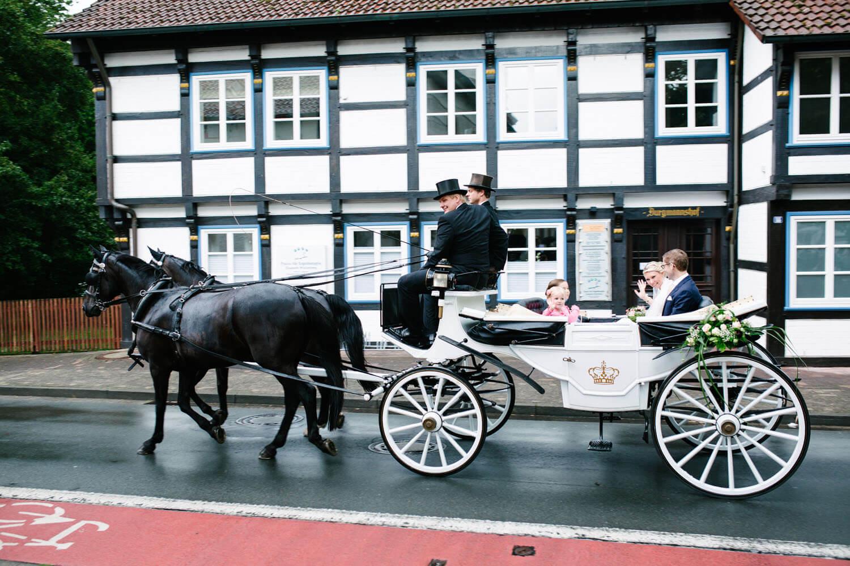 Brautpaar in der Kutsche auf dem Weg zur Feierlocation. Hochzeitsfotograf Osnabrück - Hochzeit von Maren und Kort