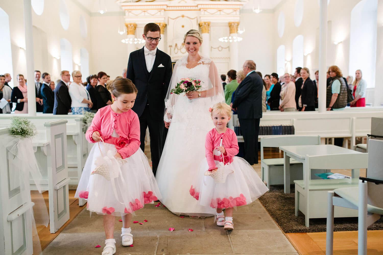 Brautpaar zieht mit Blumenkindern aus der Kirche aus. Hochzeitsfotograf Osnabrück - Hochzeit von Maren und Kort