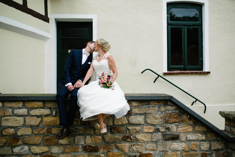 Braut und Bräutigam beim Paarshooting küssend auf einer Mauer sitzend. Hochzeitsfotograf Osnabrück - Maren und Kort