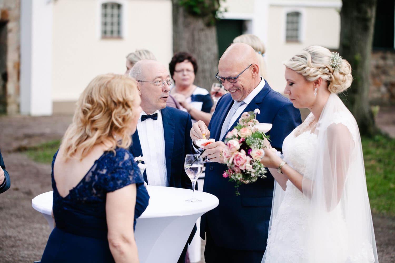 Gäste mit Braut beim Sektempfang.
