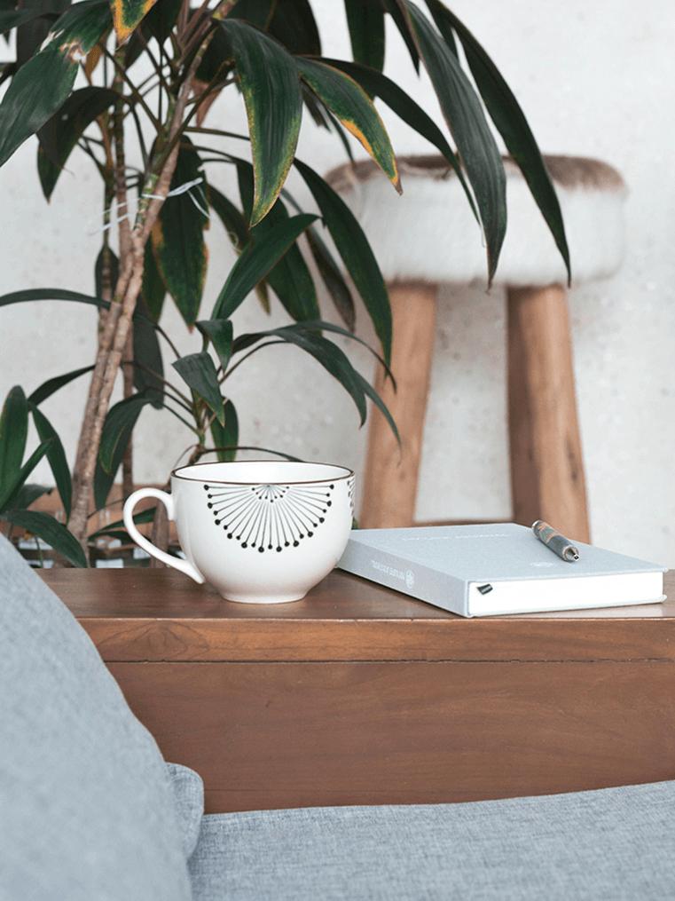 Tasse auf Tisch mit Pflanze im Hintergrund im Boho Style