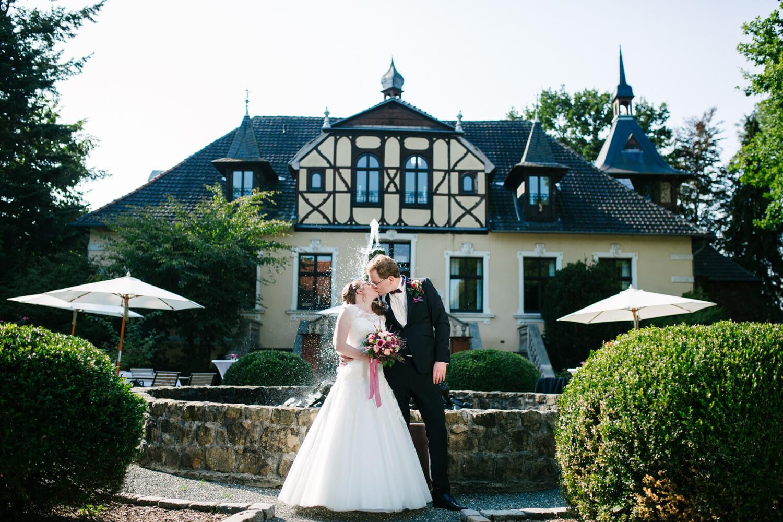 Brautpaar küssend vor dem Jagdschloss Habichtswald.