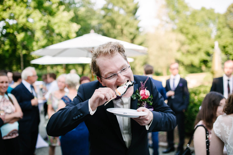 Bräutigam beißt den Pinguin aus Zucker von der Hochzeitstorte den Kopf ab.