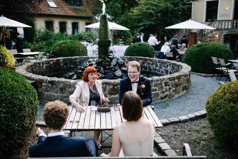 Bräutigam sitzt mit seinen Gästen am Tisch und unterhält sich angeregt.